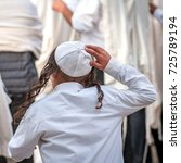 Small photo of A young Jewish Hasid boy in a traditional headdress of a kippah and with long payos.