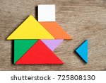 Small photo of Colorful tangram puzzle in home shape wait for fulfill on wood background (Concept for build dream house, happy family life, property investment)