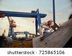 a welder in a shipyard | Shutterstock . vector #725865106