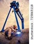 a welder in a shipyard | Shutterstock . vector #725865118