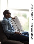 african man sitting on sofa and ... | Shutterstock . vector #725894110
