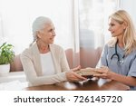 nurse and senior woman holding... | Shutterstock . vector #726145720
