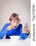 kid eating breakfast whilst... | Shutterstock . vector #726173950
