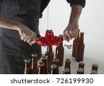Small photo of Home brewing: a craft beer brewer closing the bottles with a bottle capper.