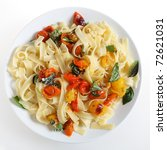 A plate of tagliatelle with grilled red and yellow cherry tomatoes tossed with oil and sprinkled with grated Parmesan and basil leaves,  viewed from above. - stock photo