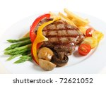 Gourmet style veal sirloin steak, served with asparagus, grilled mushrooms, cherry tomatoes, ribbons of red and yellow capsicum and fries. - stock photo