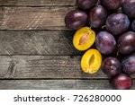 fresh blue plums on wooden table | Shutterstock . vector #726280000