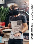 Small photo of Amazed young man wearing virtual reality goggles playing an interactive game trying to touch something at home