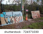 "Small photo of Two Cryptic scary spray painted signs ""You Loot, We Kill"" and ""This ain't Texas"" in the aftermath of devastating Hurricane Irma in Islamorada, in the Florida Keys"