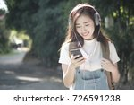Small photo of Woman walk in the park outdoor and listening to the music media entertainment. Relaxation concept. Soft picture for feeling relax with easy listening music