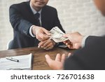 Small photo of Businessman giving money, Japanese Yen banknotes, to another business associate with a contract and calculator on his desk