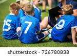 Small photo of Coach is giving kids soccer team pre-game talk. Children soccer training match. Sport motivational lecture for kids
