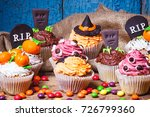 Small photo of Halloween cupcakes with decorations: tombstone, eyes and pumpkins made from confectionery mastic, soft focus background