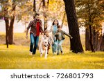 Stock photo happy family with two children running after a dog together in autumn park 726801793