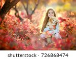 Stock photo a cute baby girl with a cute puppy is walking in an autumn forest 726868474