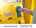 Small photo of Hand inserting ATM card into bank machine to withdraw money.