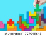 Small photo of Concept of decision making process, logical thinking. Logical tasks. Conundrum, find the missing piece of the proposed. Hand holding puzzle element. Background with colorful shapes wooden blocks
