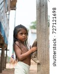 Small photo of Boca de valeria, Brazil - December 03, 2015: child girl selling sloth in village. Earning money and lifestyle concept. Poverty and childhood