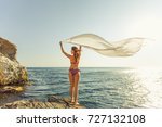 Small photo of Young woman meets sea on the shore the Black Sea in Crimea, she is looking to the horizon . People freedom style. A girl heaved up hands and holds a sarong. On a background sea waves summer. Vacation.