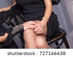 Women are holding hands. Photo of young coupleThere are two woman on the photo. One of them is sitting on a chair. Other young woman is standing alongside. She is stroking her girlfriend