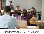 Small photo of Relieved african american entrepreneur relaxing with hands behind head, happily resting after finished work. Office worker done with task before his coworkers, colleagues are busy in shared office.