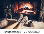 feet in woollen socks by the... | Shutterstock . vector #727208860