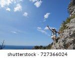woman climbs mountainside to top | Shutterstock . vector #727366024