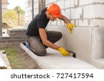 worker applies bitumen mastic... | Shutterstock . vector #727417594