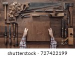 Carpenter holding a wood block and collection of vintage woodworking tools on a workbench, craftsmanship and handwork concept
