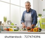smiling mature man cooking in... | Shutterstock . vector #727474396