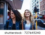 two cheerful women walking on... | Shutterstock . vector #727645240