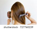 woman dries and styles her hair | Shutterstock . vector #727760239