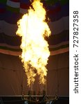 Small photo of Inside of a colorful hot air balloon as it is inflated for flight, burning burner