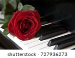 red rose on piano  | Shutterstock . vector #727936273