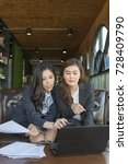Small photo of Young asian bussinesswoman are discussing their work at coffee shop. Two businesswoman working on tablet or computer, partner discuss plan or idea and opinion meeting. For Business or success concept.