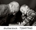 Stock photo granddad with grandson on a dark background playing chess 728497960