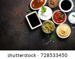 Set of sauces - ketchup, mayonnaise, mustard soy sauce, bbq sauce, pesto, mustard grains and pomegranate sauce on dark rusty stone or metal background. Top view.
