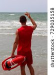 Small photo of muscular lifeguard on the shore of the sea in the beach of tourist resort exhorts to return to reckless bathers