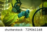 Small photo of In the Underground Drug Laboratory Clandestine Chemist Wearing Protective Mask and Coverall Holds Bag with Blue Meth Amphetamine. His Team Synthesises Illegal Substances in the Abandoned Building.