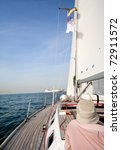 Man on sailing boat in the sea, sunny day - stock photo