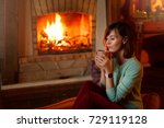 Small photo of Woman is drinking tea and warming herself by the fireplace. Young caucasian female holds cup of coffee at home. Warm house and cold winter concept.