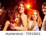 Stock photo pretty clubber dancing surrounded by her friends and looking at camera with smile 72913621