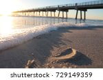 Sunrise on beach showing sand and sea foam with Jacksonville Beach Pier in background.