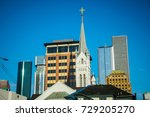 Small photo of Religious church steeple rises around Houston Texas downtown financial district tall skyscrapers , hotels , condos , and office building rise high into the sky