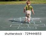 A Young Boy Playing Hop Scotch...