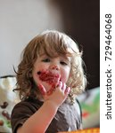 Small photo of One year old baby girl eating delicious blueberry and black currant pie with her face dirty all over.