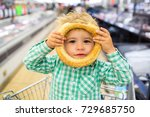 Small photo of Happy children meal. For childish menu poster. Funny food story. Great choice of food. Cute funny boy in supermarket playing with rollaway bun. Snack in children's menu. Funny kid portrait gluten free