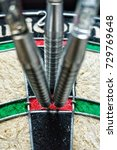 Small photo of Three darts hit the same spot on dart board. Business success and precise concept. Selective focus.