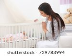 mother lulling baby in crib at... | Shutterstock . vector #729783994