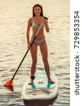 Small photo of Beautiful young woman is smiling while SUP surfing
